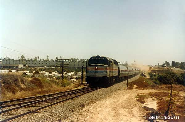 A northbound San Diegan, headed by F40PH 220, raises the dust as it enters Oceanside, CA